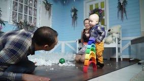 Den lyckliga familjen som håller ögonen på deras son, tar dess första steg