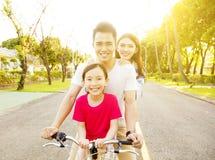 Den lyckliga familjen som har gyckel parkerar in, med cykeln Arkivbild