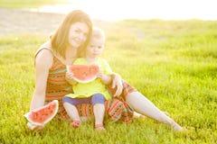 Den lyckliga familjen som har picknicken på grönt gräs parkerar in Royaltyfri Fotografi