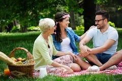 Den lyckliga familjen som har picknicken parkerar in, utomhus arkivbilder