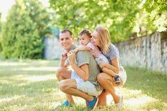 Den lyckliga familjen som ler att spela i sommar, parkerar Royaltyfri Foto