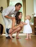 Den lyckliga familjen som ler på, behandla som ett barn stående hemmastatt Royaltyfria Foton