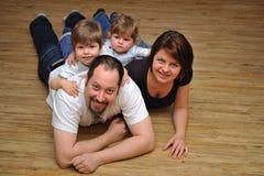 Den lyckliga familjen som ler på trä, däckar hemma royaltyfri foto
