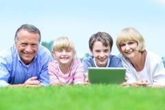 Den lyckliga familjen som ligger på gräset parkerar in Arkivfoto