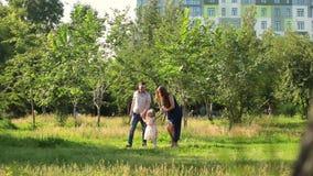 Den lyckliga familjen som in spelar, parkerar på en solig dag Virvla i dansen lager videofilmer