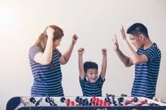 Den lyckliga familjen som spelar tabellfotboll för, kopplar av på ferie i hem royaltyfria bilder
