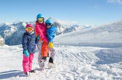 Den lyckliga familjen som tycker om vinter, semestrar i berg royaltyfria foton