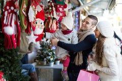 Den lyckliga familjen som väljer julgarnering på jul, marknadsför royaltyfria foton