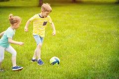 Den lyckliga familjen spelar fotboll i soligt parkerar Royaltyfri Foto