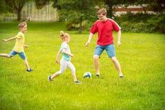 Den lyckliga familjen spelar fotboll i soligt parkerar Royaltyfri Bild
