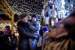 Den lyckliga familjen spenderar tid på en mässa för julgatamarknad i den gamla staden av Salzburg, Österrike Ferier, begrepp Mode Royaltyfri Fotografi