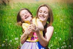 Den lyckliga familjen tar gyckel på blommaäng i sommar Royaltyfria Bilder