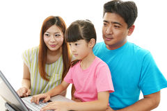 Den lyckliga familjen tycker om bärbara datorn arkivfoton