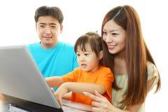 Den lyckliga familjen tycker om bärbara datorn royaltyfri foto