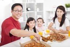 Den lyckliga familjen tycker om deras matställe Arkivfoto