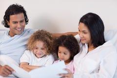 Den lyckliga familjen tycker om läsning en berättelse tillsammans Royaltyfria Bilder
