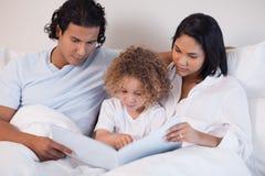 Den lyckliga familjen tycker om läsning en boka tillsammans Arkivbild