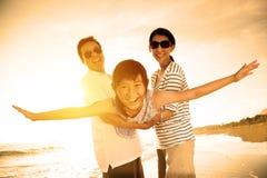 Den lyckliga familjen tycker om sommarsemester Arkivbild