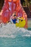 Den lyckliga familjen tycker om vattenglidbanor i Aqua Park Arkivbilder