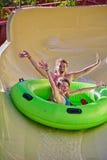 Den lyckliga familjen tycker om vattenglidbanor i Aqua Park Fotografering för Bildbyråer