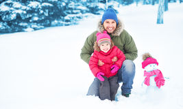 Den lyckliga familjfadern och barnflickan gör snögubben i vinter Royaltyfri Fotografi