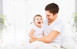 Den lyckliga familjfadern och behandla som ett barn dottern som spelar i säng Royaltyfri Foto