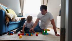 Den lyckliga familjfarsamamman och behandla som ett barn 2 år som spelar lego i deras ljusa vardagsrum Ultrarapid som skjuter den lager videofilmer