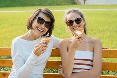Den lyckliga familjhelgen, den utomhus- ståenden av mamman och dottern med glass i parkerar på en bänk arkivbilder
