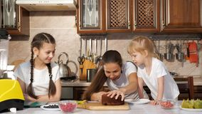 Den lyckliga familjmamman och döttrar lagar mat födelsedagkakan tillsammans lager videofilmer