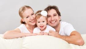Den lyckliga familjmodern, fadern, barn behandla som ett barn dottern hemma på soffan som spelar och skrattar Arkivbilder