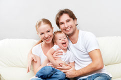 Den lyckliga familjmodern, fadern, barn behandla som ett barn dottern hemma på soffan som spelar och skrattar Royaltyfria Foton