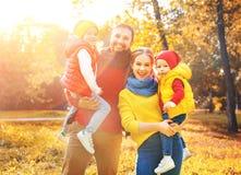 Den lyckliga den familjmodern, fadern och barn på en höst går Royaltyfri Foto