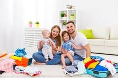 Den lyckliga familjmodern, fadern och två barn packade resväskor fo Royaltyfri Bild