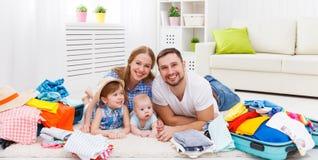 Den lyckliga familjmodern, fadern och två barn packade resväskor fo Arkivbilder