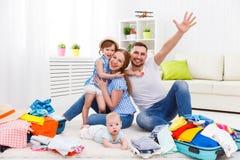 Den lyckliga familjmodern, fadern och två barn packade resväskor fo Royaltyfri Fotografi