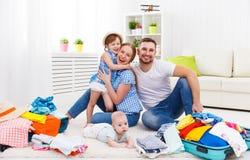 Den lyckliga familjmodern, fadern och två barn packade resväskor fo Arkivfoton