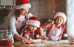 Den lyckliga familjmodern och barn bakar kakor för jul Arkivfoton