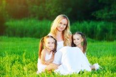Den lyckliga familjmodern och barn kopplar samman systrar på äng i summe Arkivfoto