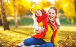 Den lyckliga familjmodern och barndottern på höst går royaltyfria bilder