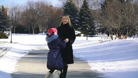 Den lyckliga familjmodern och barndottern som har gyckel som spelar på vintern, går utomhus arkivfilmer