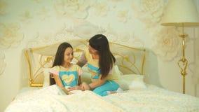 Den lyckliga familjmodern och barndottern spelar och skrattar i säng stock video