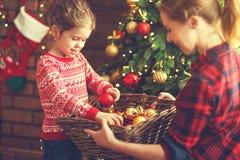Den lyckliga familjmodern och barnflickan dekorerade julgranen royaltyfri foto