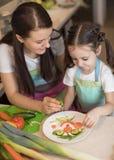 Den lyckliga familjmodern och barnflickan förbereder sund mat, dem improviserar tillsammans i köket Royaltyfri Fotografi