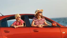 Den lyckliga familjmodern och barnflickan g?r till sommarloppturen i bil arkivfoton
