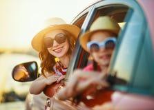 Den lyckliga familjmodern och barnflickan g?r till sommarloppturen i bil royaltyfri fotografi
