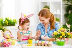 Den lyckliga familjmodern och barnflickan målar ägg för påsk royaltyfria bilder