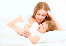 Den lyckliga familjmodern och behandla som ett barn att sova i säng Fotografering för Bildbyråer