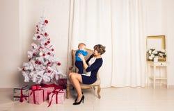 Den lyckliga familjmodern och behandla som ett barn den lilla sonen som hem spelar på julferier Ferier för ` s för nytt år Litet  Arkivbilder