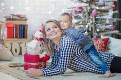 Den lyckliga familjmodern och behandla som ett barn den lilla sonen som hem spelar på julferier Ferier för ` s för nytt år Litet  Arkivfoto