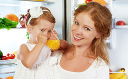 Den lyckliga familjmodern och behandla som ett barn dottern som in dricker orange fruktsaft Royaltyfria Bilder